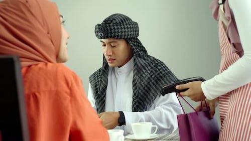 Asian Muslim Man Using Mobile Phone Payment