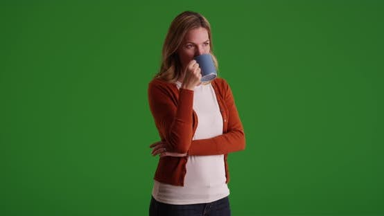 Thumbnail for Caucasian woman drinking from coffee mug on green screen