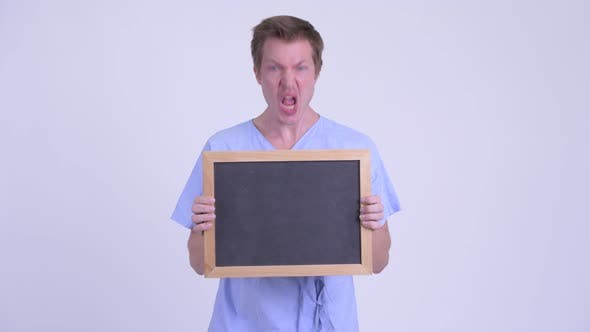 Thumbnail for Portrait of Young Man Patient Holding Blackboard and Looking Shocked
