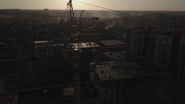 Cover Image for Construction Site at Sunset. Silhouette of a Construction Crane Near the Building