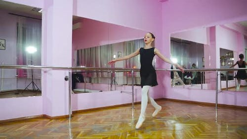 Slow motion. Professional ballerina perform pirouette in the ballet hall. A little dancer.