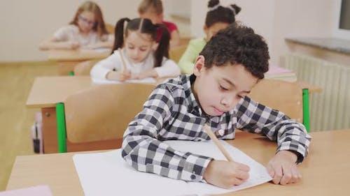Boy Writing in Copybook in Classroom.