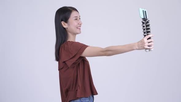 Cover Image for Happy Beautiful Asian Woman Vlogging and Showing Phone