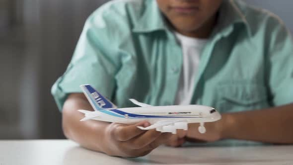 Biracial Male Child Playing with Toy Airplane in Free Time, Childhood Dream