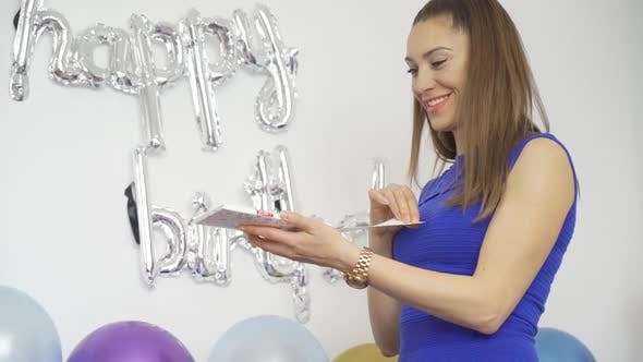 Young Woman Opening a Birthday Card with Confetti Bomb Inside