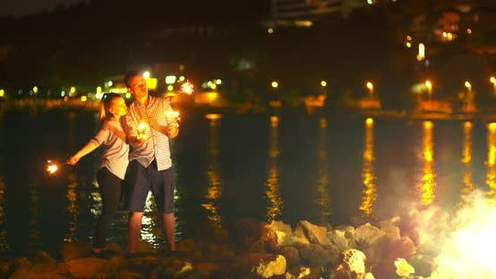 Cover Image for Couple Holding Sparklers at Seashore