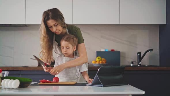 Mother in Gray Apron Stands in Kitchen
