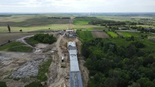 A Large Bridge Is Being Built With The Help Of Heavy Machinery And A Crane