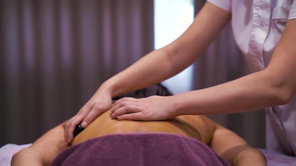 Rückenmassage mit Steinen im Wellness Spa