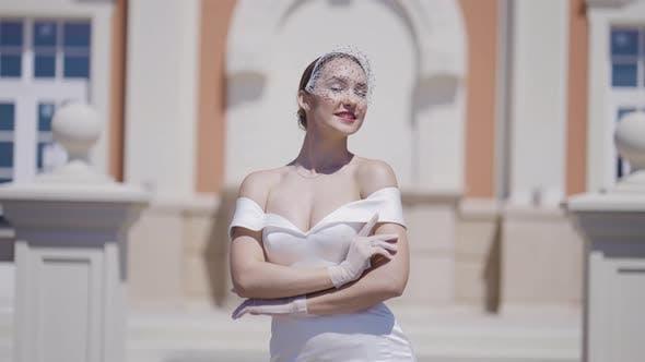Elegant bride poses on background of old building