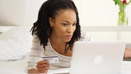 Thumbnail for Happy black woman smiling with laptop and credit card