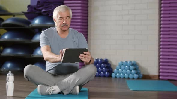 Thumbnail for Aged Man Using Tablet in Sports Hall