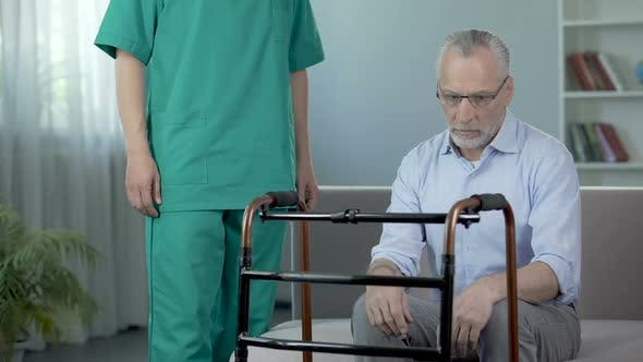 Thumbnail for Old depressed male sitting on couch and looking on walking frame, nursing home