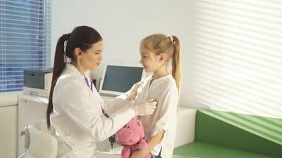 Young Doctor Pediatrician Examines Child Applies Stethoscope to Child's Body