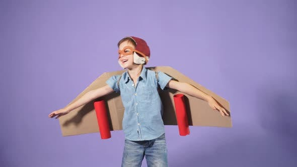 Pilot Boy with Cardboard Plane Isolated Over Blue Background
