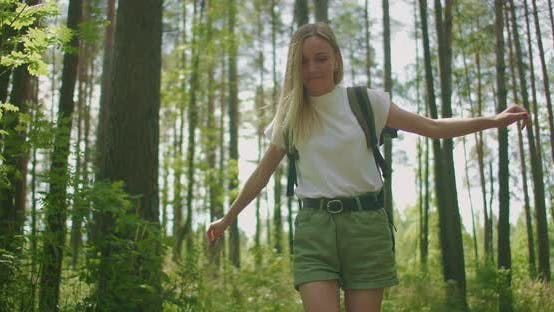 Thumbnail for Blonde Woman Walks Through the Woods with a Backpack Passing Through a Log