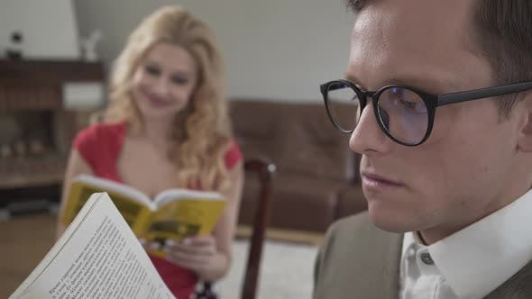 Thumbnail for Young Modestly Dressed Man in Glasses Reading the Book in the Foreground While Curly Blond Woman