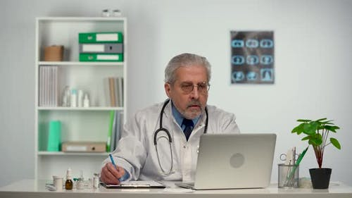 Aged Male Doctor Reviews the Patient's Analyzes on a Laptop and Makes Notes in His Medical History