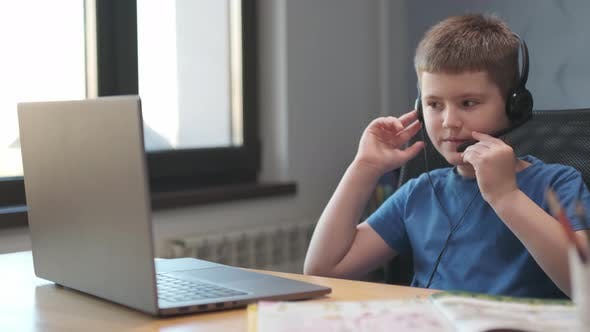 Portrait of a young boy teaching lessons online at a distance using laptop and internet via video