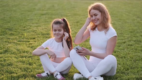 Thumbnail for Mom and Girl Are Sitting on the Lawn and Listening To Music
