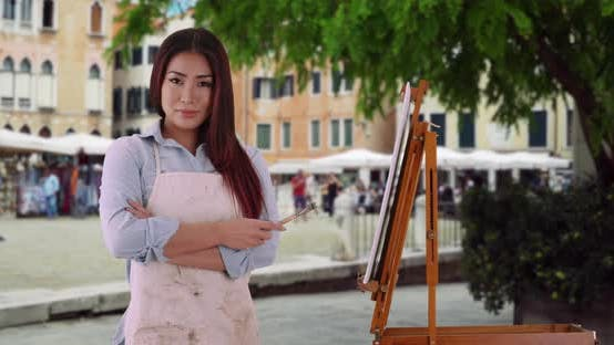 Thumbnail for Beautiful Asian woman in painter's smock standing on Venice street with tourism