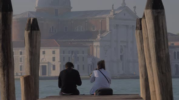 Thumbnail for Couple Sitting on the Pier and Drinking Alcohol. Venice, Italy