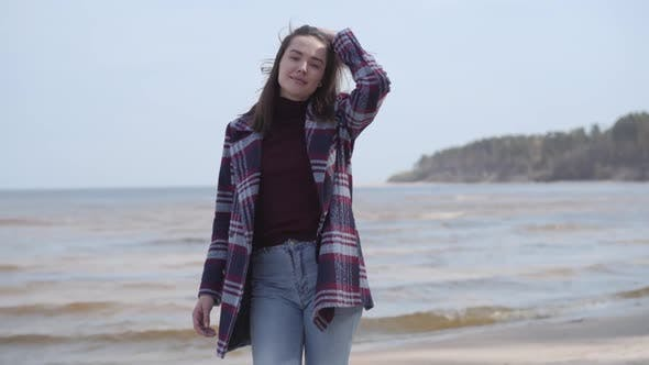 Thumbnail for Portrait of Cheerful Young Brunette Girl Walking on Sandy Beach and Smiling. Young Millennial