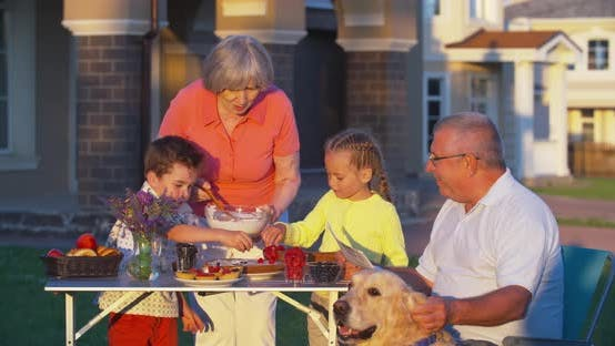 Thumbnail for Kids Helping Grandmother to Set Picnic Table