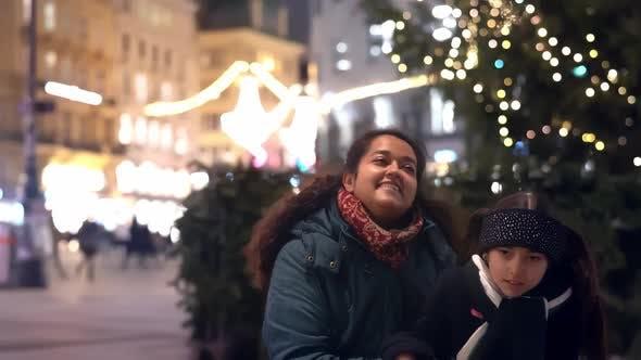 Fröhliches kleines Mädchen und ihre Mutter im Freien in einem Stadtzentrum zur Weihnachtszeit