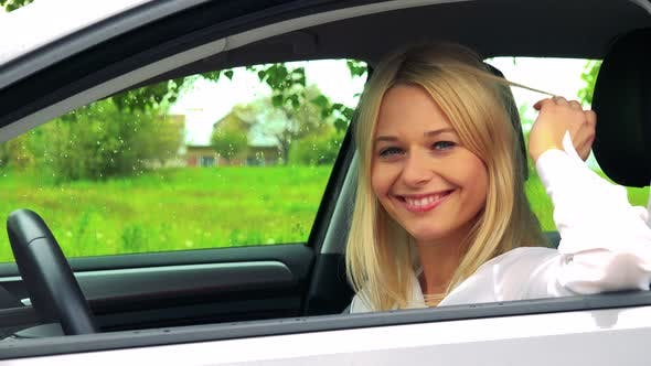 Young Attractive Blond Woman Sits in the Car and Smiles To the Camera