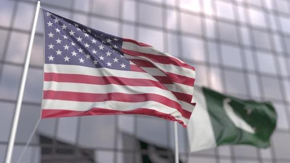 Waving Flags of the USA and Pakistan Near Modern Skyscraper