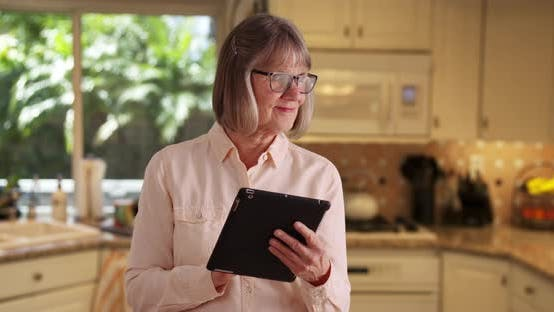 Charming senior woman using handheld tablet device to browse online in kitchen