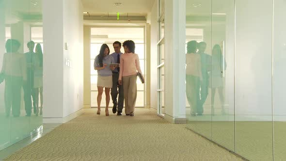 Thumbnail for Three business people walking down hallway