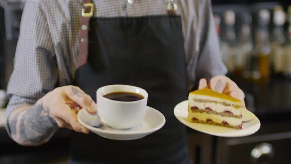 Thumbnail for Tattooed Barista Holding Cup of Americano and Cake
