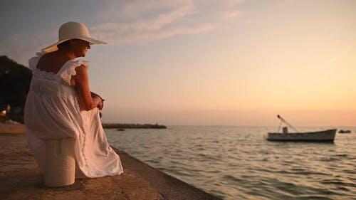Senior Caucasian Woman Seating in Marina and Enjoying Sunset