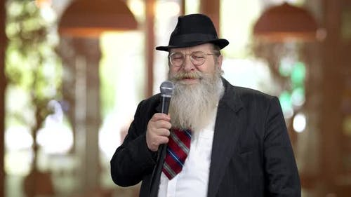 Old Bearded Man in Suit Talking with Microphone