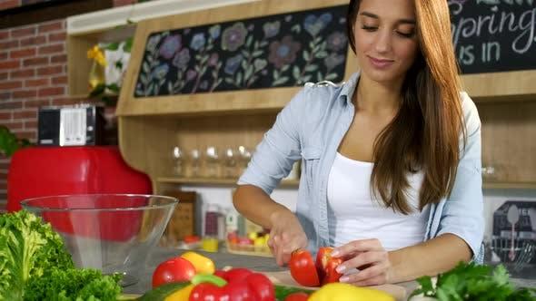 Thumbnail for Attraktive junge Frau in Licht Jeans Shirt Schneiden Tomaten und Puts in Glas Schüssel für Salat