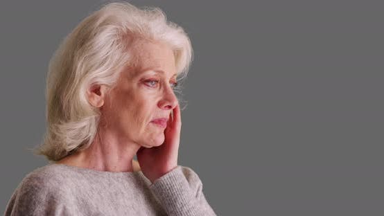 Close up of older woman with headache touching her temples on grey background