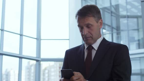 Thumbnail for Mid-Aged Businessman Messaging on Smartphone