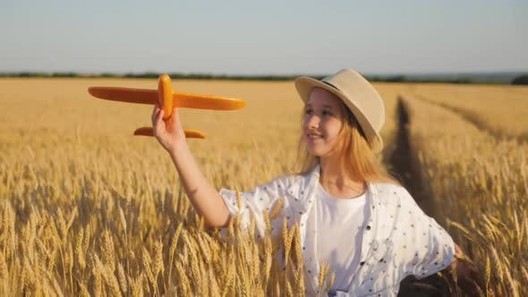 Happy Girl Child Run on Wheat Field with an Airplane