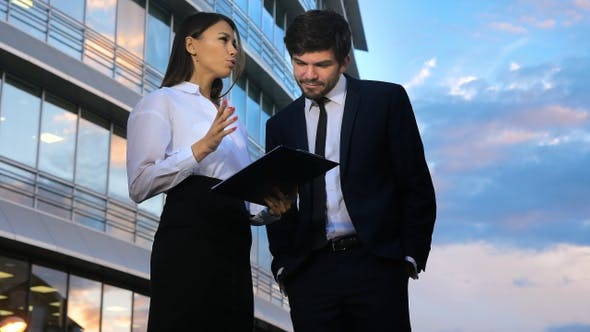 Thumbnail for Elegant woman secretary showing documents to her boss giving