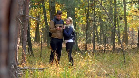 Thumbnail for A Hiking Couple Stands in the Middle of a Meadow in a Forest and Takes Selfies with a Smartphone