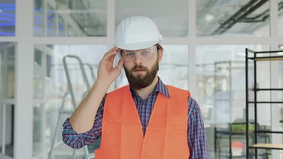 Thumbnail for Builder in Special Uniform Taking off Protective Goggles and Looking at Camera
