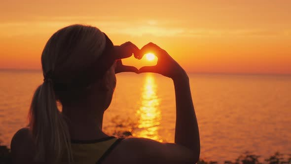 Thumbnail for A Woman Looks at the Sea Where the Sun Sets, Shows a Heart-shaped Figure