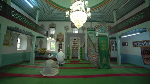 Muslim Mosque Teacher in a Robe and Turban at the Small Historic Wooden Masjid