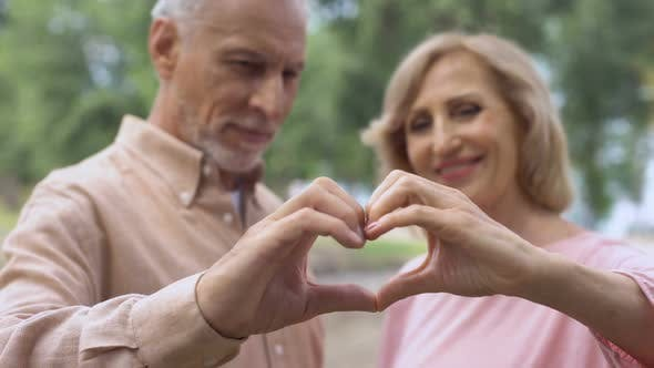 Thumbnail for Smiling Aged Couple Showing Heart Sign, Love Symbol, Happy Marriage, Affection
