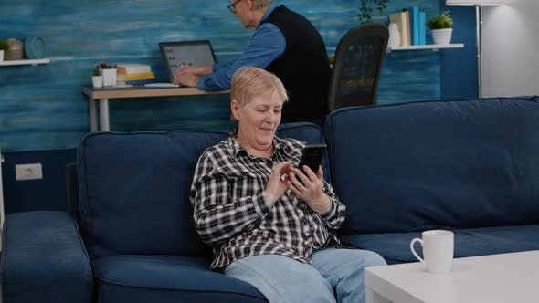 Middle Aged Woman Relaxing Holding Smartphone Reading News