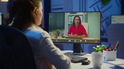 Manager Talking with Coworker During Video Conference at Midnight