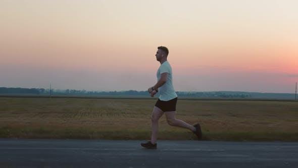 Thumbnail for Starkes muskulöses Joggen auf Asphaltstraße bei Sonnenuntergang