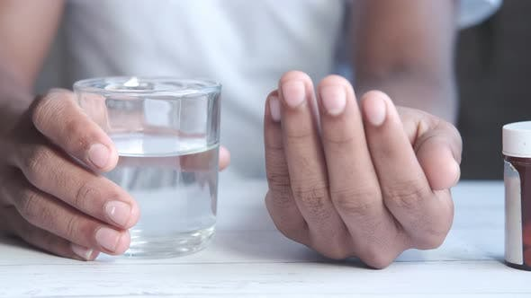 Young Man Holding Pills and Glass of Water with Copy Space